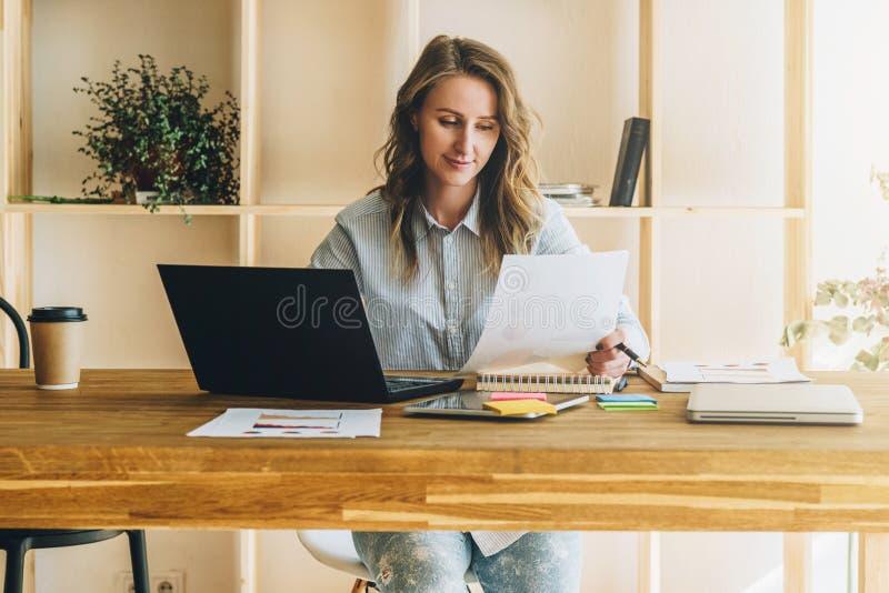 De jonge onderneemstervrouw zit bij keukenlijst, lezend documenten, gebruikslaptop, het werken, het bestuderen stock foto's