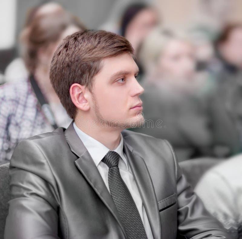 De jonge ondernemers luisteren aan de lezing, zittend in de zaal van het commerciële centrum stock foto