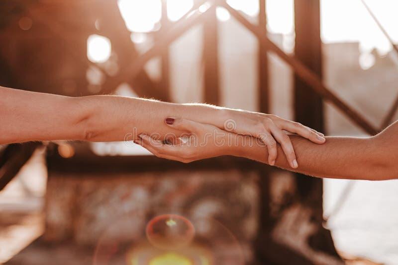 De jonge onherkenbare lesbische handen van de paarholding bij zonsondergang in openlucht Levensstijl en trotsconcept De liefde is stock foto
