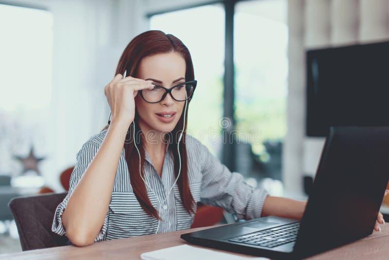 De jonge online mededeling van de ondernemersvrouw door laptop stock afbeelding