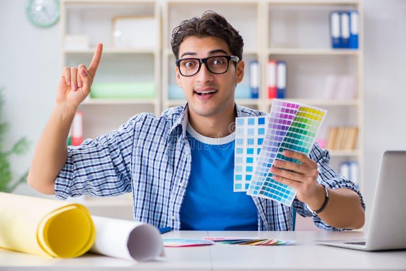 De jonge ontwerper die aan nieuw project werken en kleuren kiezen stock fotografie