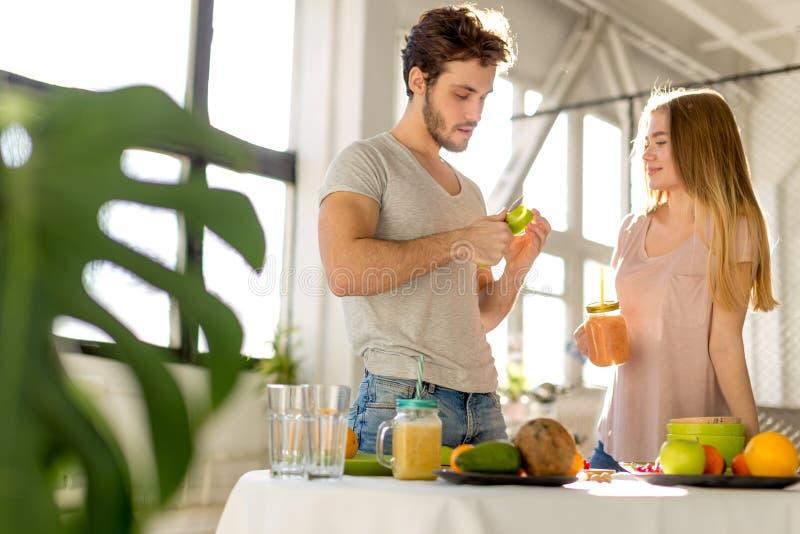 De jonge ontzagwekkende gebaarde mens pelt een appel en gaat naar giveit naar een meisje royalty-vrije stock afbeeldingen