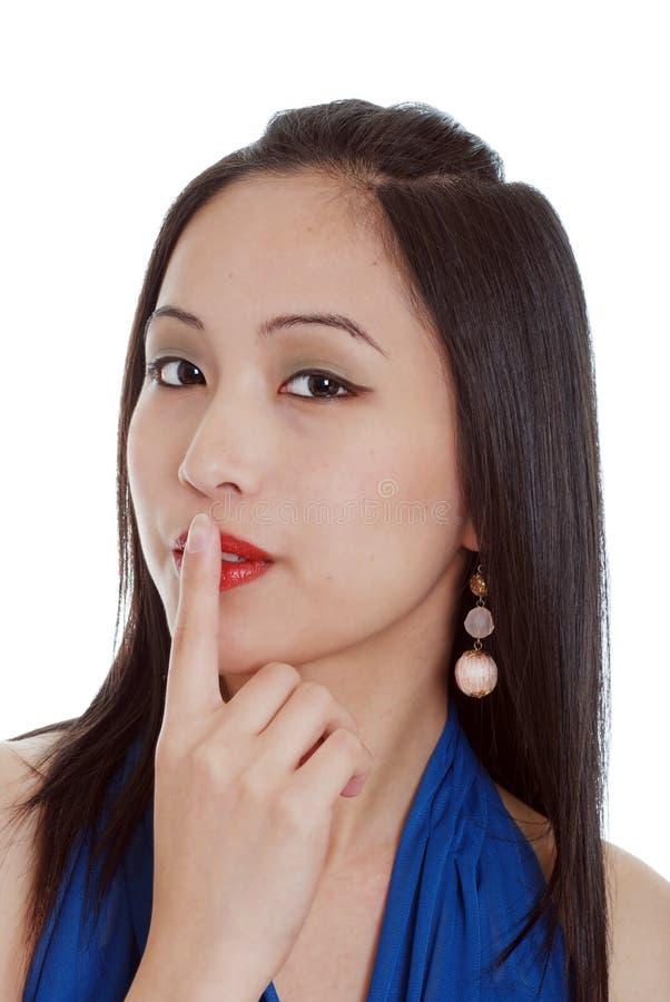 De jonge oosterse vrouw vertelt u stil om te zijn stock foto
