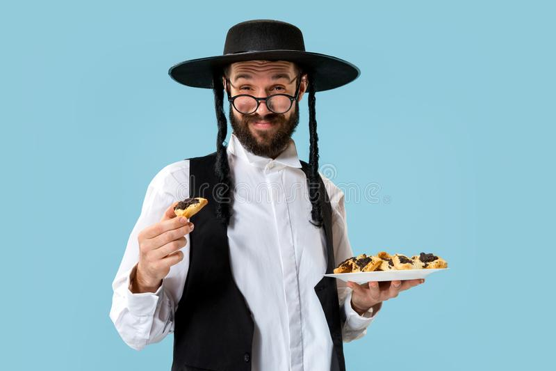 De jonge orthodoxe Joodse man met zwarte hoed met Hamantaschen-koekjes voor Joods festival van Purim royalty-vrije stock afbeelding