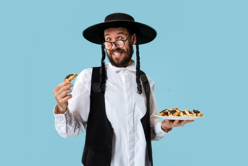 De jonge orthodoxe Joodse man met zwarte hoed met Hamantaschen-koekjes voor Joods festival van Purim royalty-vrije stock afbeeldingen