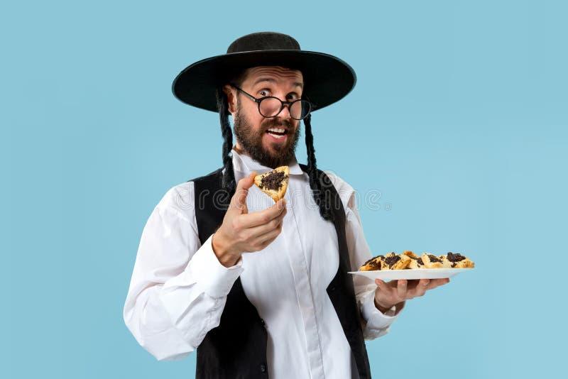 De jonge orthodoxe Joodse man met zwarte hoed met Hamantaschen-koekjes voor Joods festival van Purim stock afbeelding