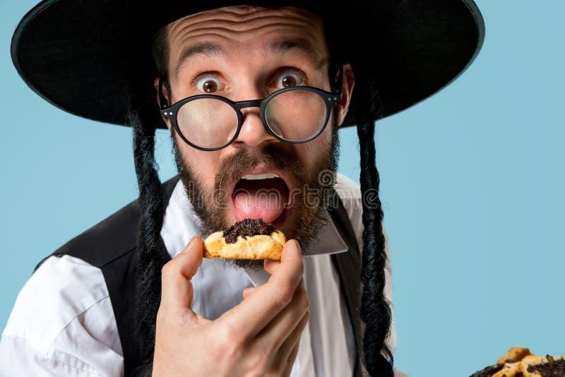 De jonge orthodoxe Joodse man met zwarte hoed met Hamantaschen-koekjes voor Joods festival van Purim stock fotografie