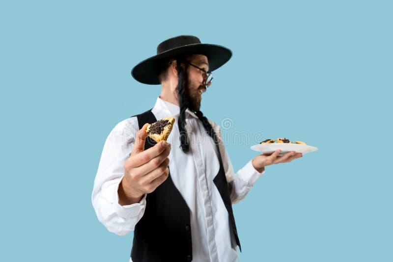 De jonge orthodoxe Joodse man met zwarte hoed met Hamantaschen-koekjes voor Joods festival van Purim royalty-vrije stock fotografie