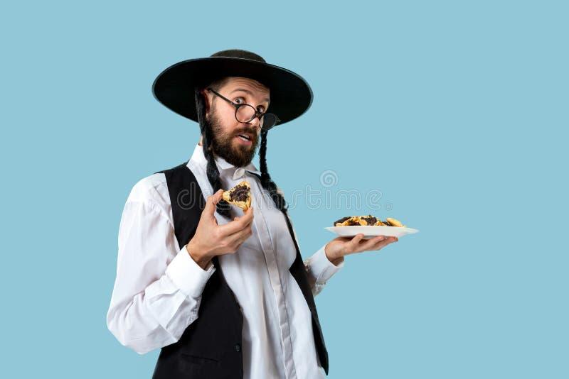De jonge orthodoxe Joodse man met zwarte hoed met Hamantaschen-koekjes voor Joods festival van Purim stock foto's