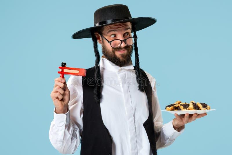 De jonge orthodoxe Joodse man met zwarte hoed met Hamantaschen-koekjes voor Joods festival van Purim stock afbeeldingen