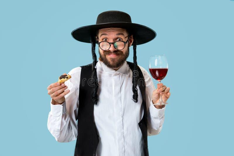 De jonge orthodoxe Joodse man met zwarte hoed met Hamantaschen-koekjes voor Joods festival van Purim royalty-vrije stock foto