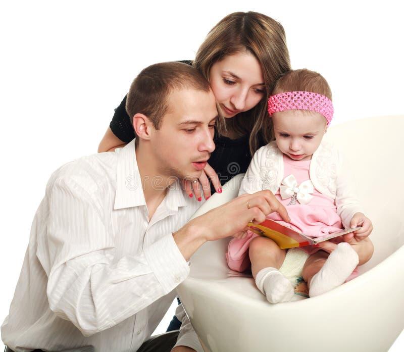 De jonge ouders en de baby lezen het tijdschrift royalty-vrije stock fotografie