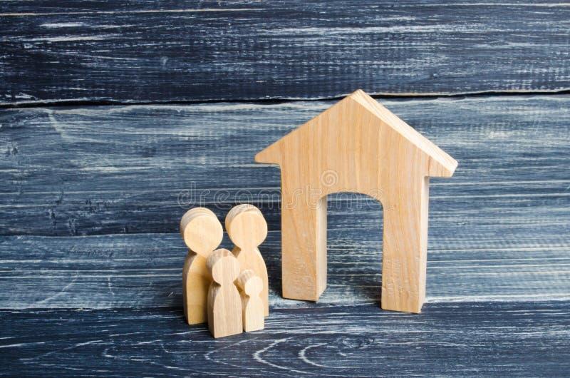 De jonge ouders en een kind bevinden zich dichtbij hun huis Concept die onroerende goederen, en een huis kopen verkopen Betaalbar stock afbeeldingen
