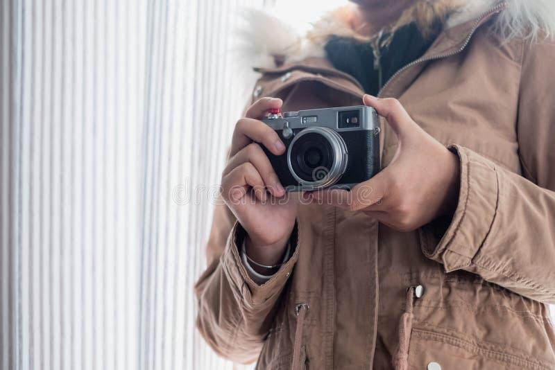 De jonge overjas van de meisjesslijtage met het houden van retro camera stock foto