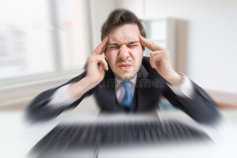 De jonge overwerkte mens wordt vermoeid door met compuiter te werken en aan hoofdpijn te lijden stock afbeelding