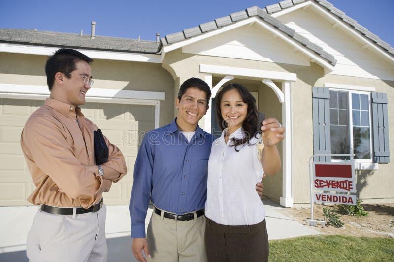 De jonge paar het kopen sleutels van de huisholding stock afbeelding