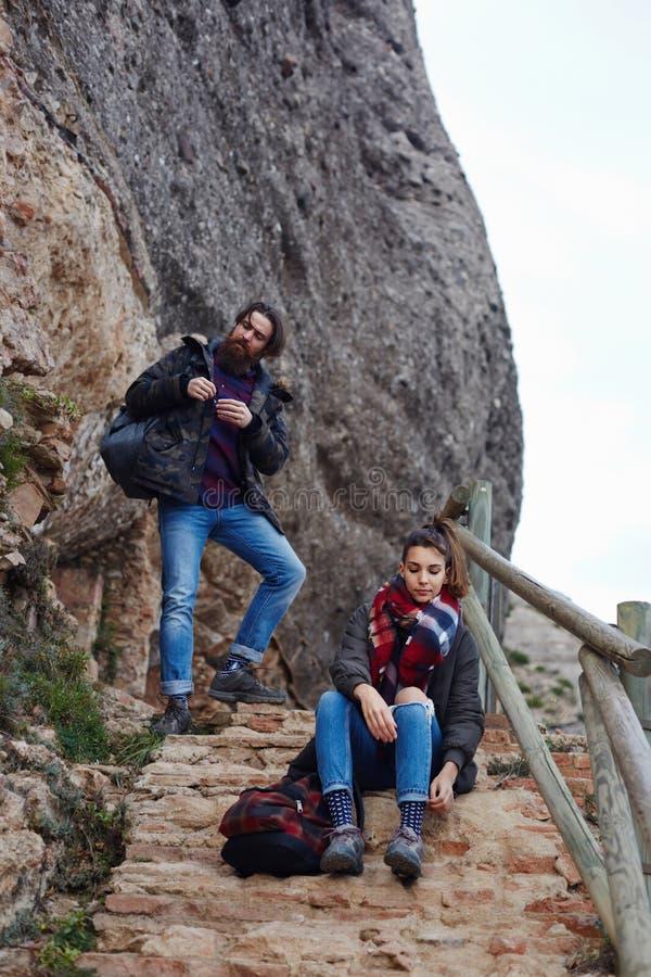De jonge paarreizigers hielden om te rusten op alvorens een berg te beklimmen royalty-vrije stock afbeelding