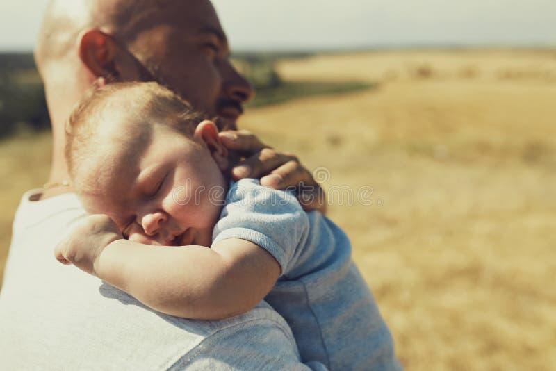 De jonge papa houdt een pasgeboren baby die op zijn schouder, in aard lopen de gelukkige vader draagt borrels en een t-shirt inte stock foto