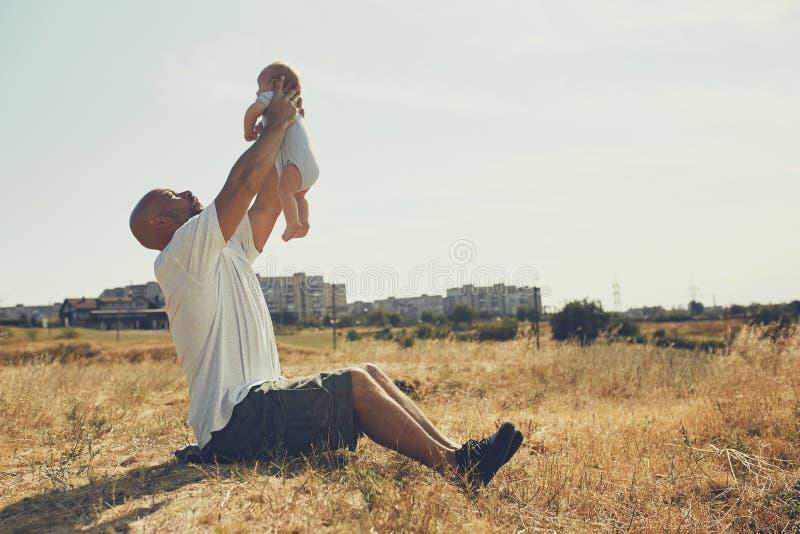 De jonge papa houdt een pasgeboren baby op zijn uitgestrekte wapens de gelukkige vader draagt borrels en een t-shirt Internationa stock fotografie