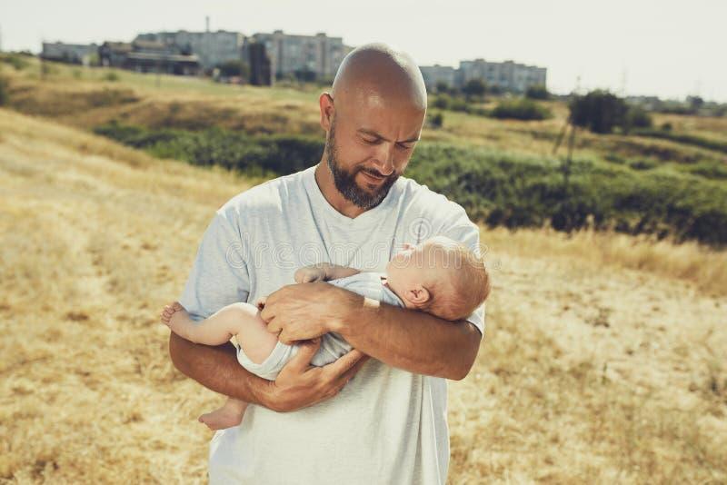 De jonge papa houdt een pasgeboren baby terwijl het lopen in aard de gelukkige vader draagt borrels en een t-shirt Internationale royalty-vrije stock fotografie