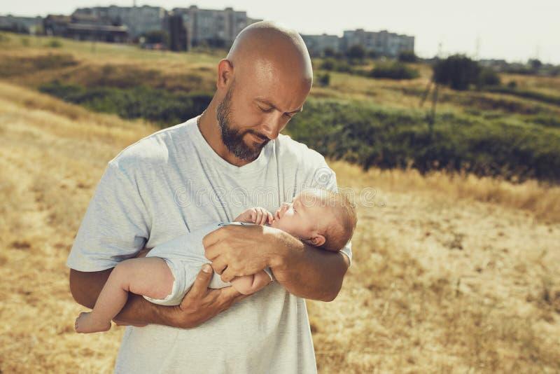 De jonge papa houdt een pasgeboren baby terwijl het lopen in aard de gelukkige vader draagt borrels en een t-shirt Internationale royalty-vrije stock foto