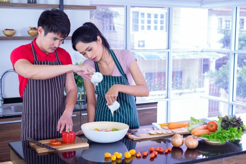 De jonge Paren Aziaat in schort, maken het koken samen in keuken met hoogtepunt van ingrediënt op lijst stock foto