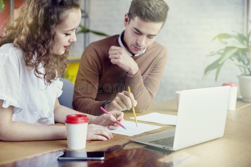 De jonge partnersmensen verzamelden zich samen, besprekend creatief idee in bureau Gebruikend moderne laptop, die koffie hebben royalty-vrije stock foto's