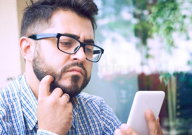 De jonge peinzende gebaarde zakenman in glazen, kleedde zich in plaidoverhemd, zittend bij lijst in koffie en gebruikssmartphone  royalty-vrije stock fotografie