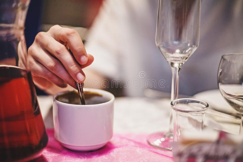 De jonge personen overhandigen het mengen van suiker in een kop van koffie stock afbeeldingen