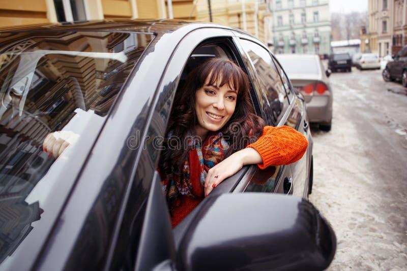 De jonge plaatsing van de vrouwenbestuurder in auto en het glimlachen royalty-vrije stock foto's