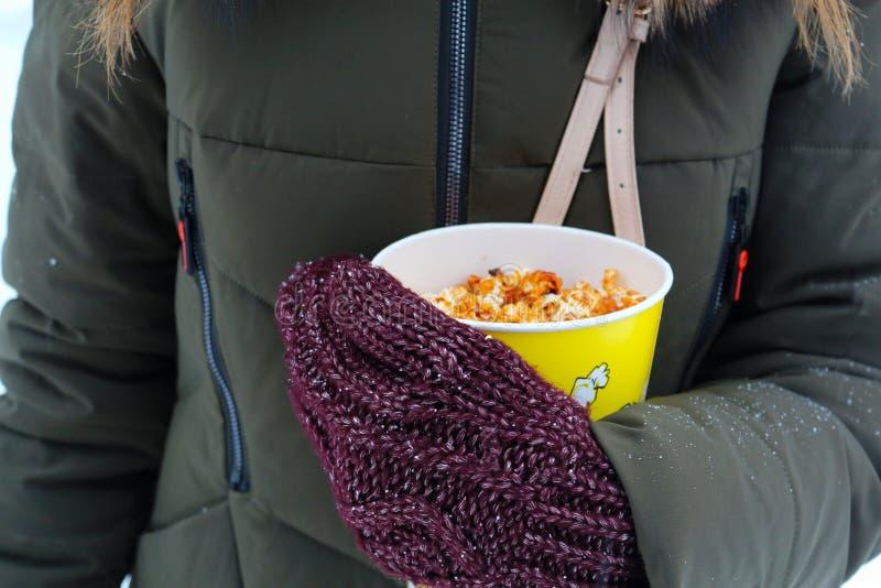 De jonge popcorn van de vrouwenholding in de winter, in vuisthandschoenen stock foto's