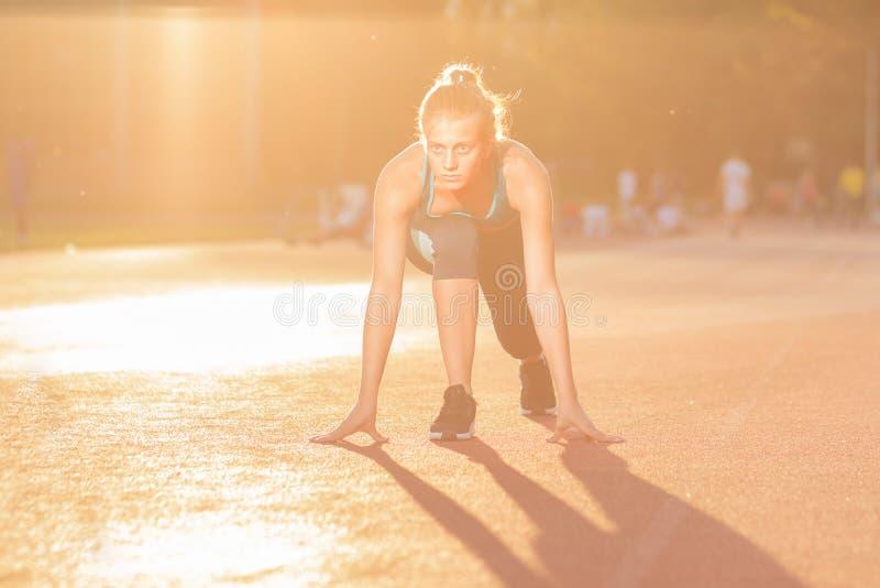 De jonge positie van het de sprinterbegin van de meisjestiener stock foto's