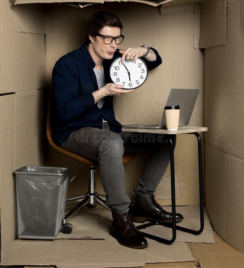 De jonge positieve manager houdt klok stock afbeeldingen