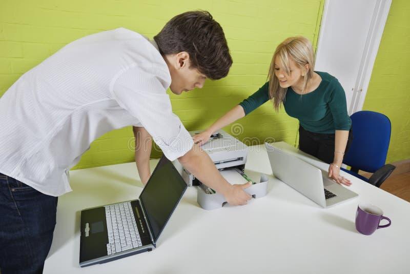 De jonge printer van de zakenluivestiging met laptops bij bureau stock fotografie