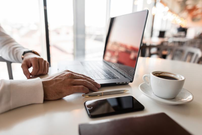 De jonge professionele mens van de managerYoung professionele manager in een overhemd die aan laptop zitting bij de lijst in het  royalty-vrije stock afbeeldingen