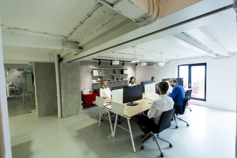 De jonge programmeurs zitten en werken in modern bureau stock afbeeldingen