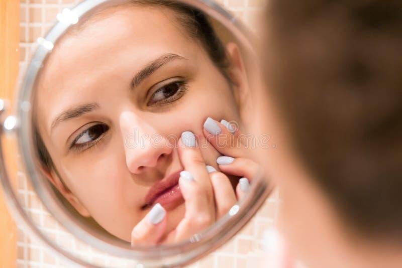 De jonge pukkel van de meisjessamendrukking op het fergezicht voor een badkamersspiegel Schoonheid skincare en het concept van de royalty-vrije stock fotografie