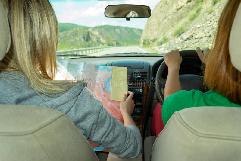 De jonge reis van vrouwentoeristen door auto en zit in de voorzetels, heeft een kaart in hun handen en zij maakt een route, de tw stock afbeeldingen