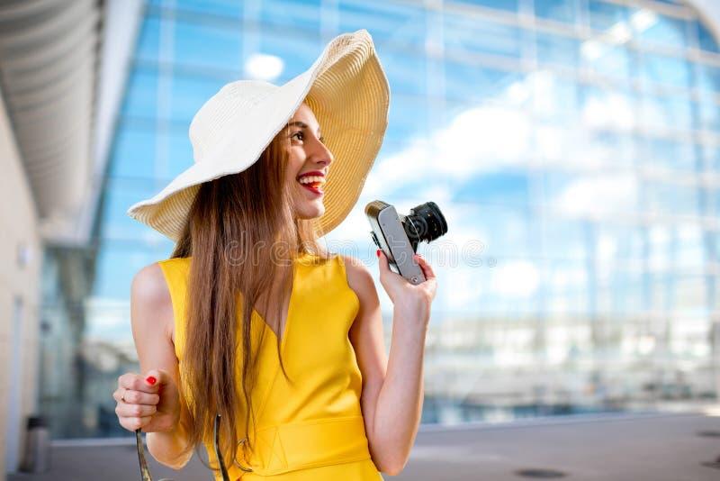 De jonge reizende vrouw met fotocamera en Panama kleedden zich in ye stock foto
