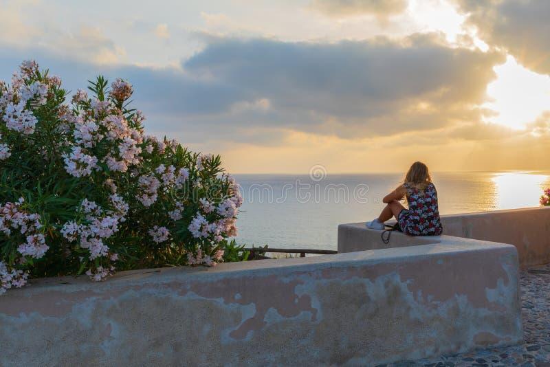 De jonge reiziger van de hipstervrouw zonsondergang bekijken en het mooie zeegezicht die in de zomervakantie met een vooruitzicht stock fotografie