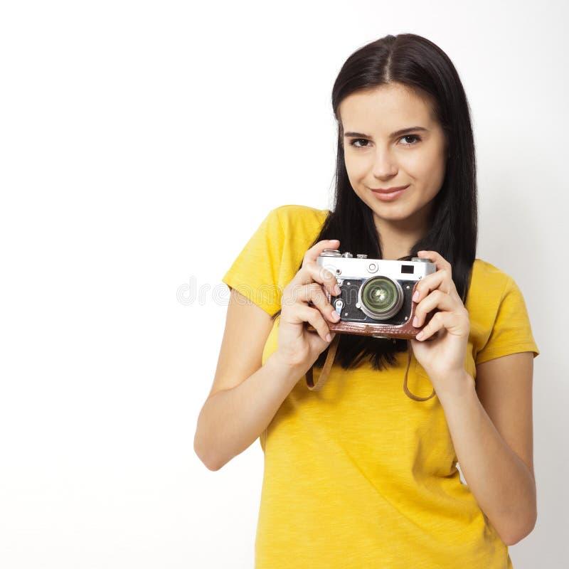De jonge retro camera van de Vrouwenholding tegen witte achtergrond stock fotografie