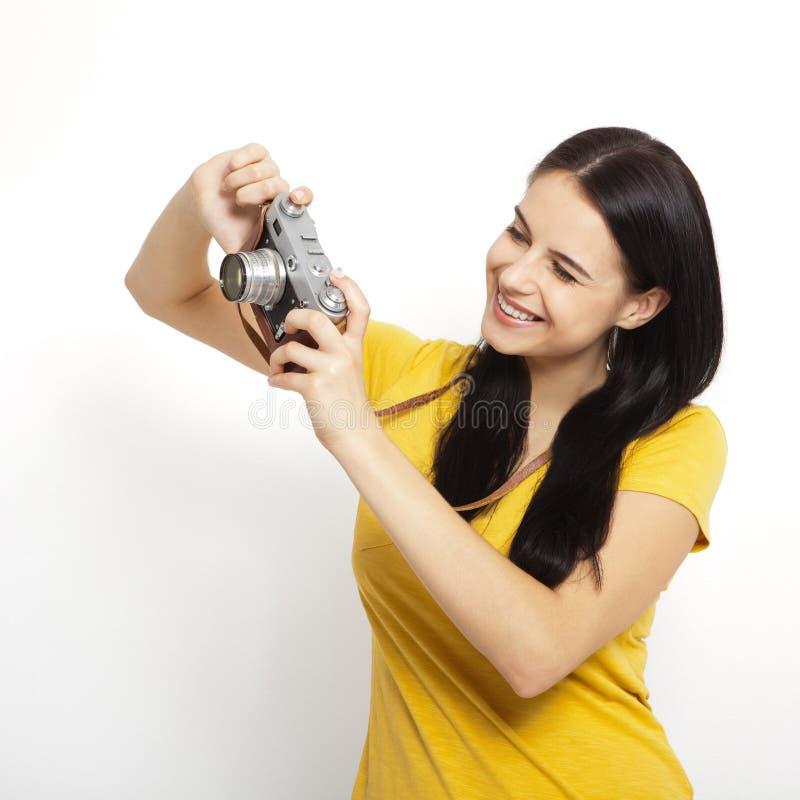 De jonge retro camera van de Vrouwenholding tegen witte achtergrond royalty-vrije stock foto