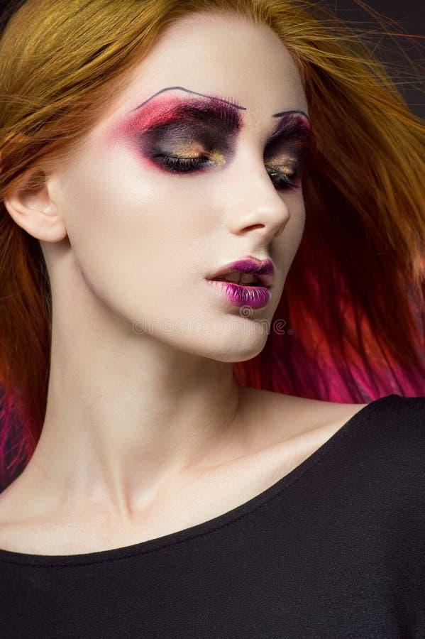 De jonge roodharige vrouw met kleurrijk maakt omhoog stock afbeeldingen