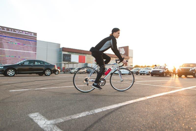 De jonge ruiter berijdt een fiets in de stad op de achtergrond van de zonsondergang en bekijkt de camera stock afbeelding