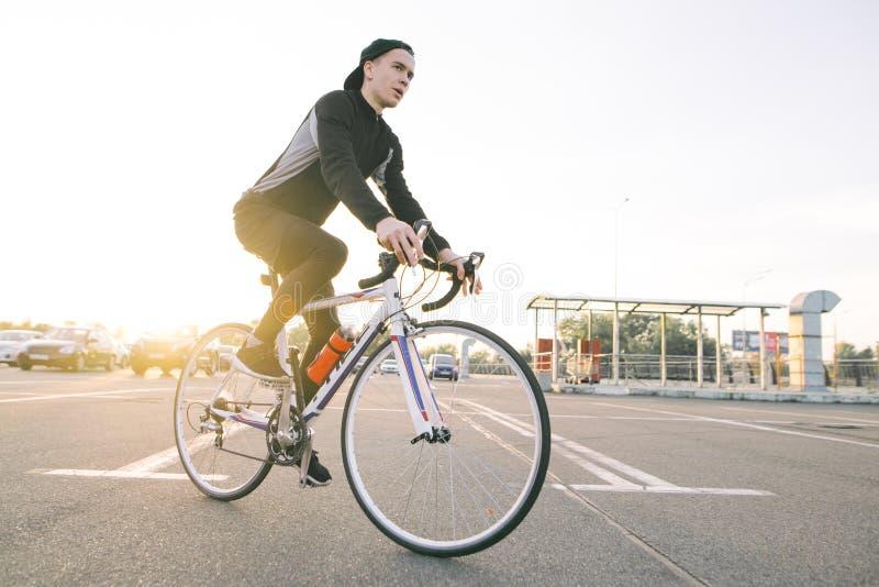De jonge ruiter in donkere fiets draagt een fiets op een straatachtergrond en zonneschijn in de zonsondergang stock afbeeldingen