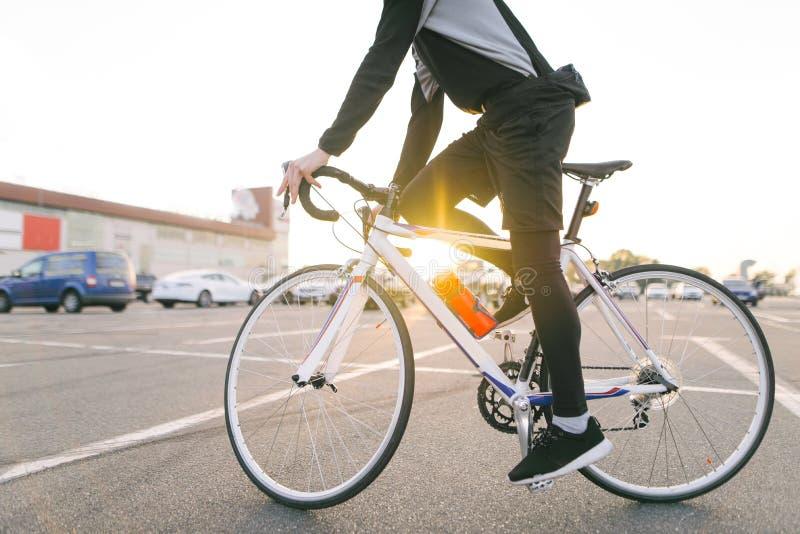 De jonge ruiter in donkere fiets draagt een fiets op een straatachtergrond en zonneschijn in de zonsondergang stock foto's