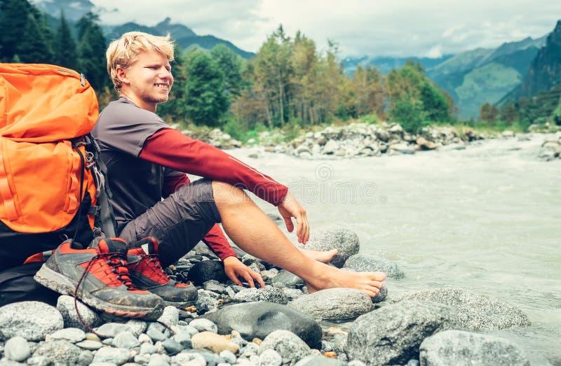 De jonge rust van de toeristenmens op de bank van de bergrivier royalty-vrije stock foto