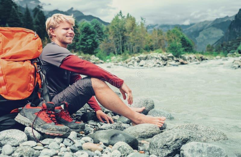 De jonge rust van de toeristenmens op de bank van de bergrivier stock foto's