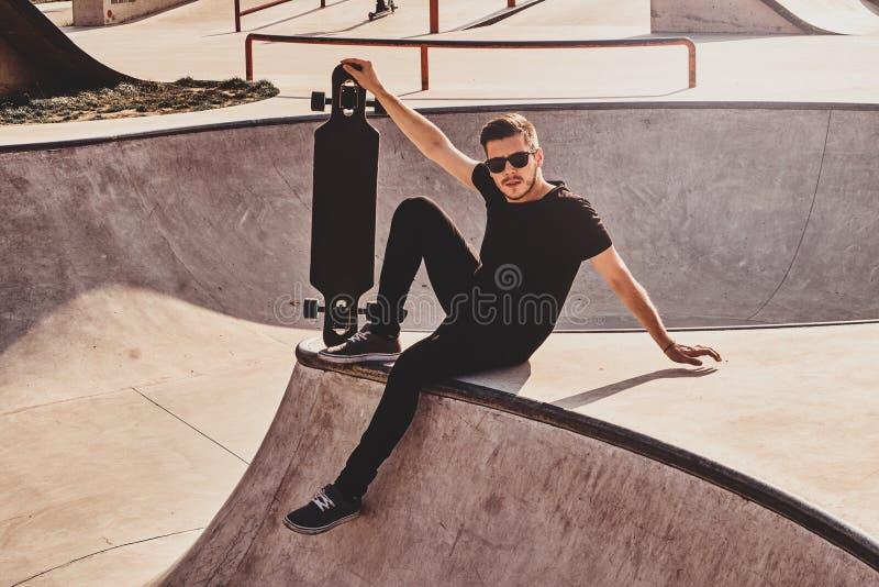 De jonge schaatser in zonnebril zit op de helling met zijn eigen longboard stock foto's
