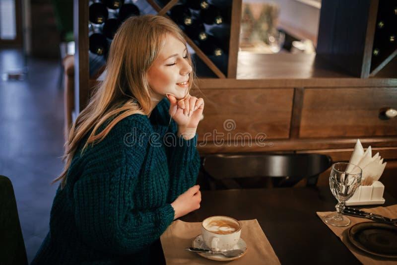 De jonge schitterende nadenkende vrouwelijke het drinken thee of de koffie in koffie winkelt terwijl het genieten van van haar al stock foto